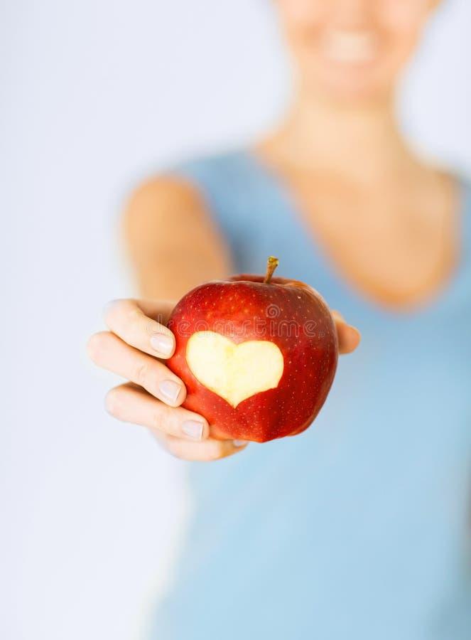 Mano della donna che tiene mela rossa con forma del cuore immagini stock