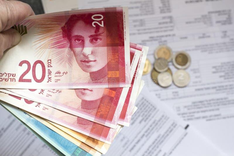 Mano della donna che tiene un mazzo di nuove banconote israeliane dello shekel fotografia stock libera da diritti