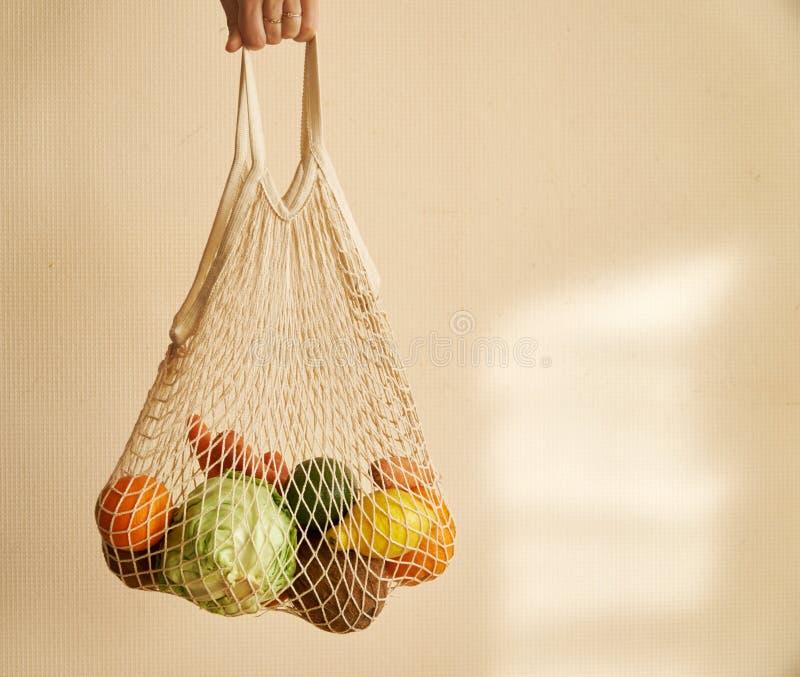 Mano della donna che tiene un sacchetto della spesa della corda con le verdure, frutti nei toni terrosi caldi, spreco zero immagine stock