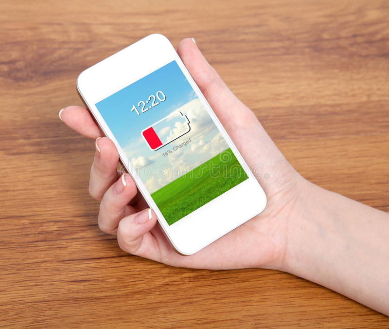 Mano della donna che tiene un telefono bianco di tocco con la batteria bassa su un SCR fotografia stock libera da diritti
