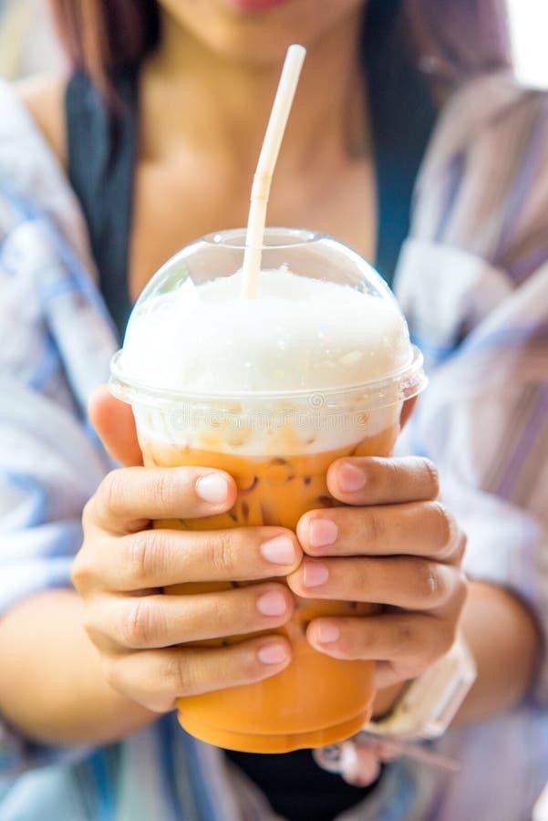 Mano della donna che tiene un vetro di caffè ghiacciato nel caffè immagini stock