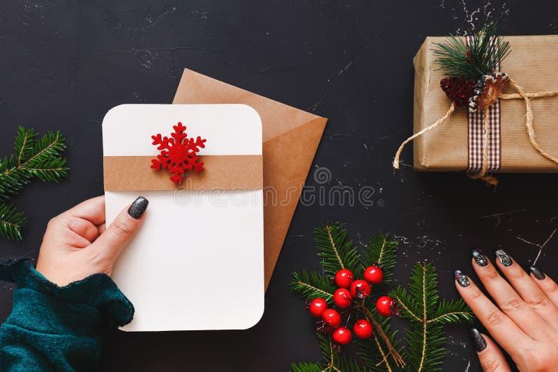 Mano della donna che tiene una lettera sopra la tavola di Natale fotografia stock