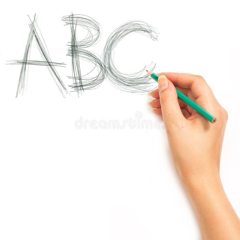 Mano della donna che tiene una matita e che scrive ABC immagine stock libera da diritti