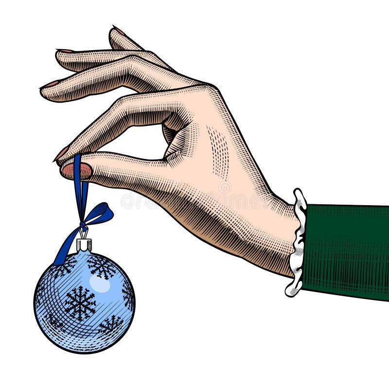 Mano della donna che tiene una palla dell'albero di Natale royalty illustrazione gratis