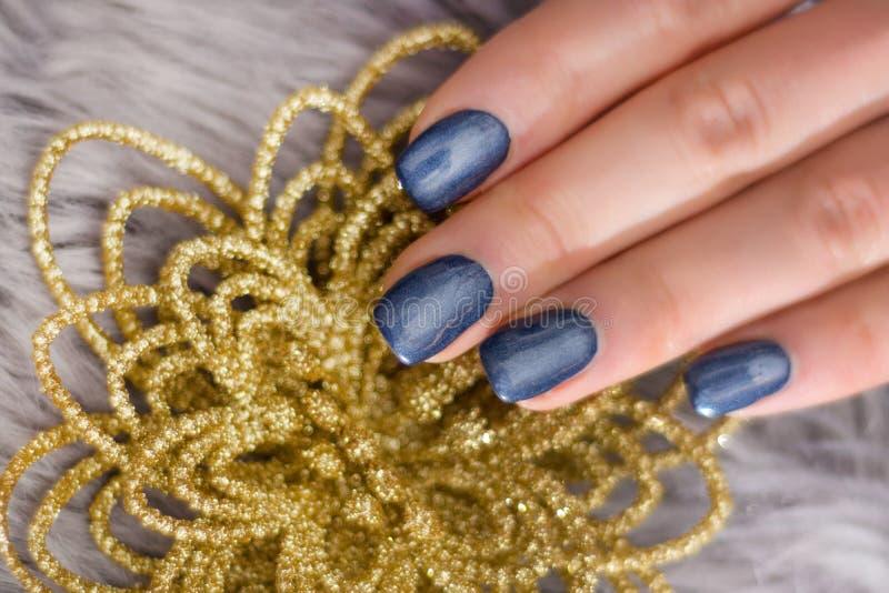 Mano della donna con il gel della lucidatura di unghie dei blu navy sulle unghie e sul fiore dorato decorativo immagini stock