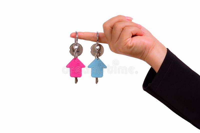 Mano della donna con keychain due sotto forma della casa fotografia stock libera da diritti