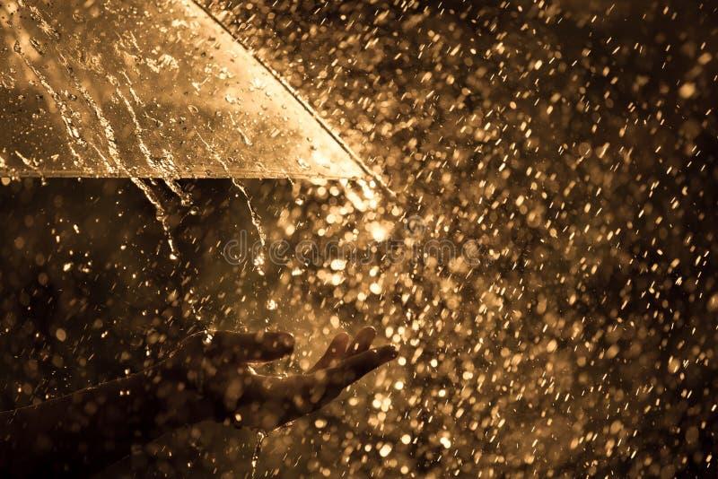 Mano della donna con l'ombrello nella pioggia fotografia stock