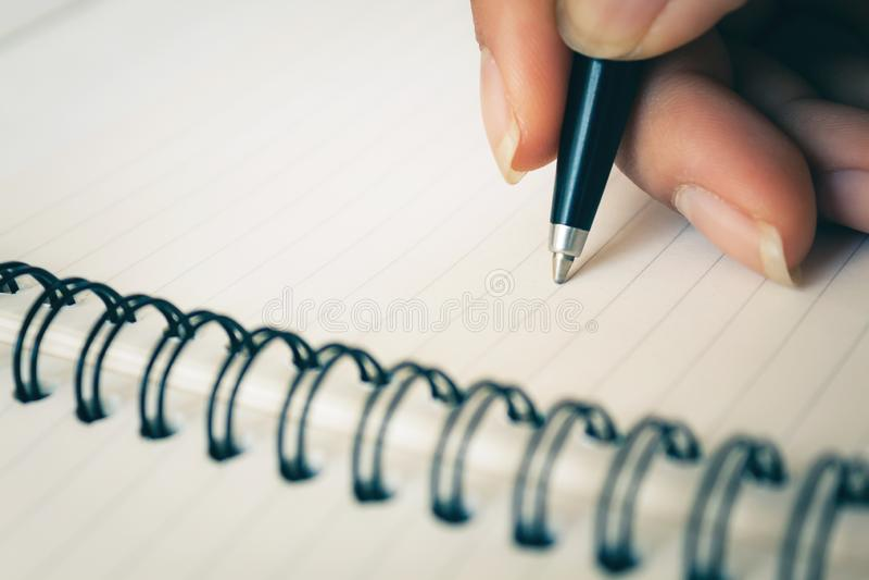 Mano della donna con scrittura della penna sul taccuino bianco immagine stock