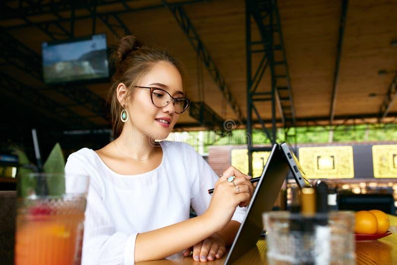 Mano della donna della corsa mista delle free lance che indica con lo stilo sullo schermo convertibile del computer portatile nel immagine stock