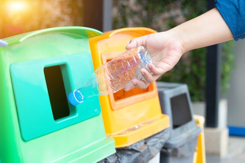 Mano della donna del primo piano che getta bottiglia di acqua di plastica vuota nei rifiuti Ricicli lo scomparto fotografie stock libere da diritti