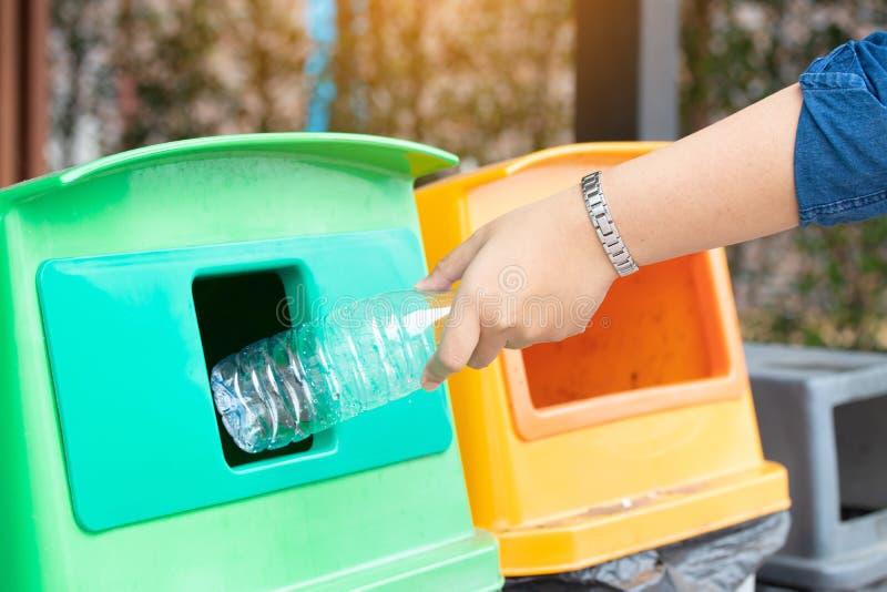 Mano della donna del primo piano che getta bottiglia di acqua di plastica vuota nei rifiuti Ricicli lo scomparto fotografia stock libera da diritti