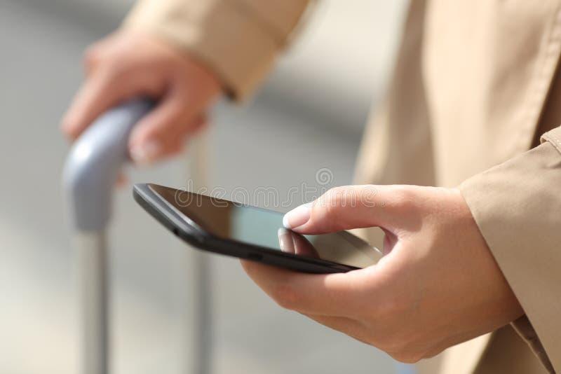 Mano della donna del viaggiatore che consulta uno smartphone e che tiene una cassa del vestito immagine stock libera da diritti