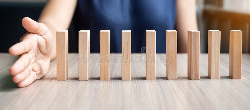 Mano della donna di affari che ferma i domino di legno di caduta immagini stock