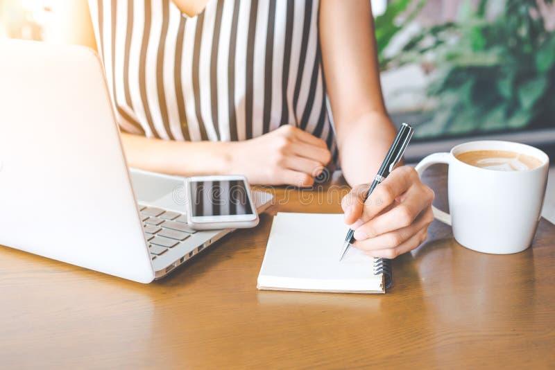 Mano della donna di affari che funziona ad un computer e che scrive sull'noteped con una penna