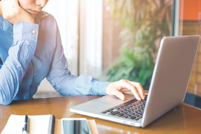 Mano della donna di affari che funziona con un computer portatile nell'ufficio fotografia stock libera da diritti