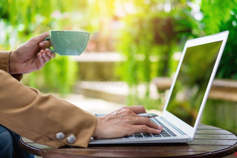 mano della donna di affari che funziona facendo uso del computer portatile sulla tavola in giardino immagine stock libera da diritti