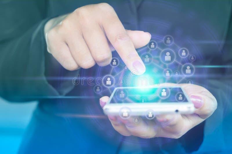 Mano della donna di affari che tocca sullo schermo dello Smart Phone con l'icona di tecnologia della gente immagine stock