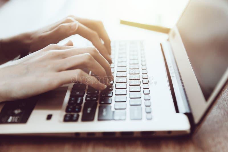 Mano della donna di affari del primo piano al computer portatile del computer fotografia stock
