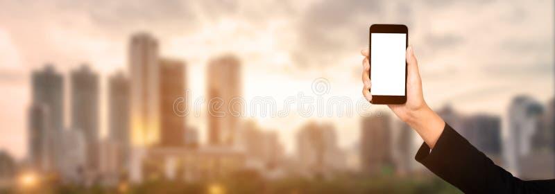 Mano della donna di affari facendo uso dello smartphone mobile con lo schermo bianco, ci immagine stock