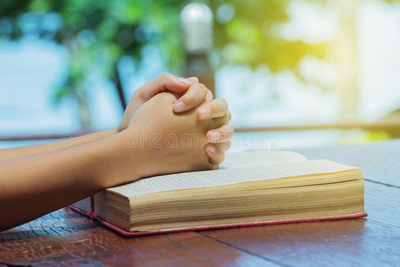 Mano della donna disposta su una veglia di preghiera della bibbia La lettura ed il soggiorno religiosi calmano immagine stock libera da diritti