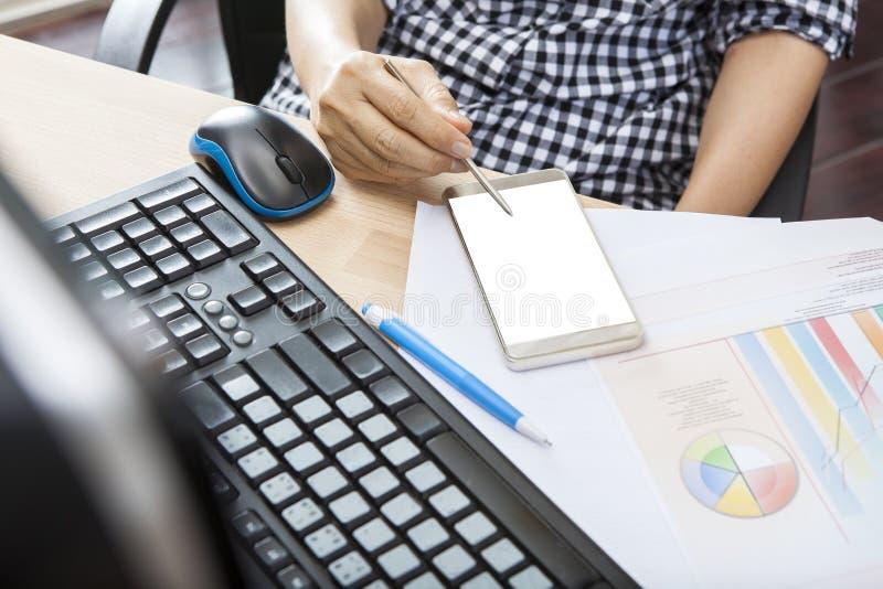 Mano della donna lavoratrice con la penna di scrittura dello Smart Phone sul contatto della s fotografia stock