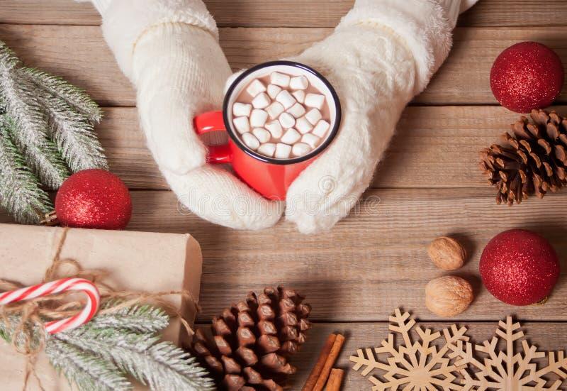 Mano della donna in muffole bianche che tiene una tazza rossa di cacao natalizio con marshmallows Le decorazioni natalizie sullo  immagine stock libera da diritti