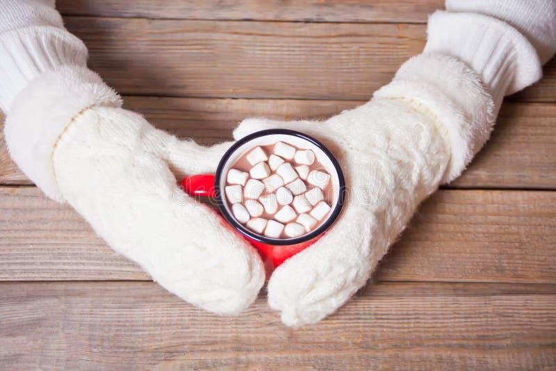 Mano della donna in muffole bianche che tiene una tazza rossa di cacao natalizio con marshmallows fotografie stock