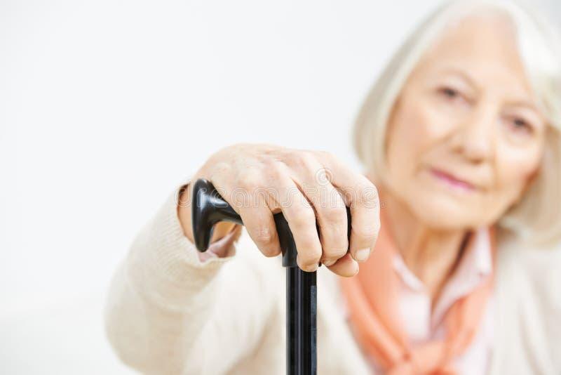 Mano della donna senior anziana sulla canna immagine stock