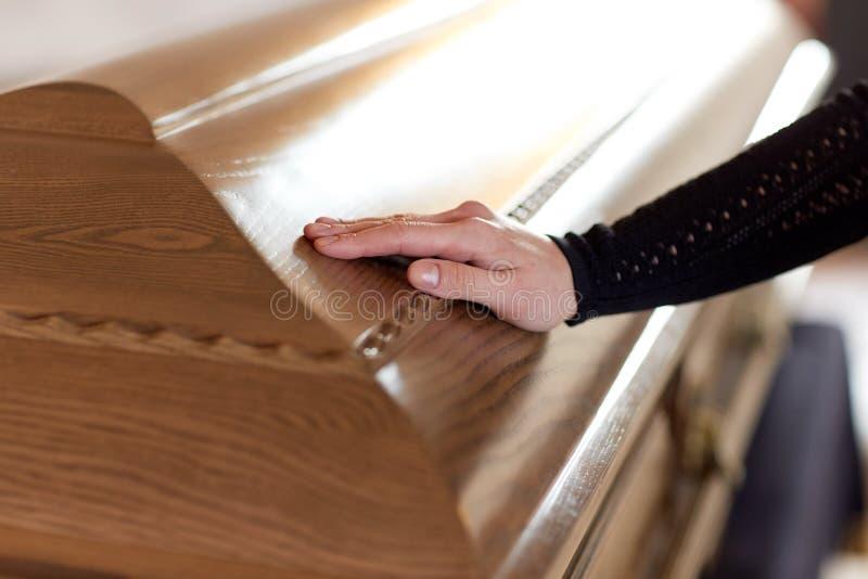 Mano della donna sul coperchio della bara al funerale in chiesa fotografia stock