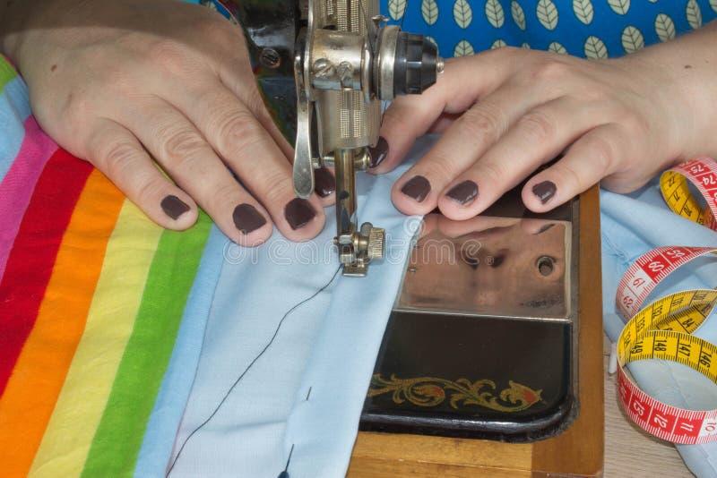 Mano della donna sulla macchina per cucire Lavoro del sarto da donna sulla macchina per cucire Tessuto di cucito di hobby come co fotografia stock libera da diritti