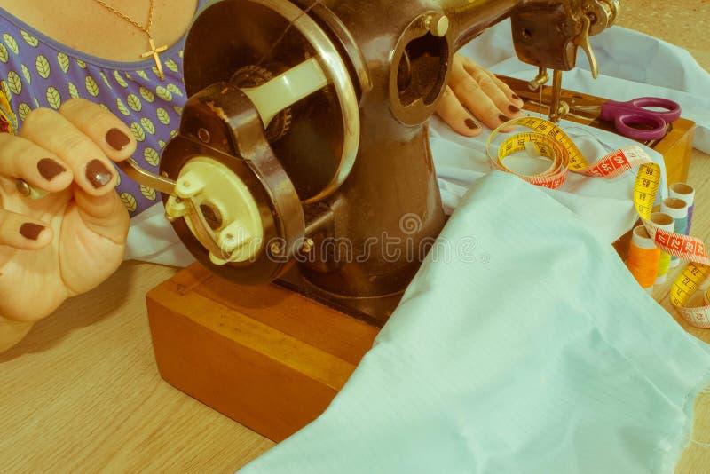 Mano della donna sulla macchina per cucire Lavoro del sarto da donna sul machi di cucito fotografia stock libera da diritti