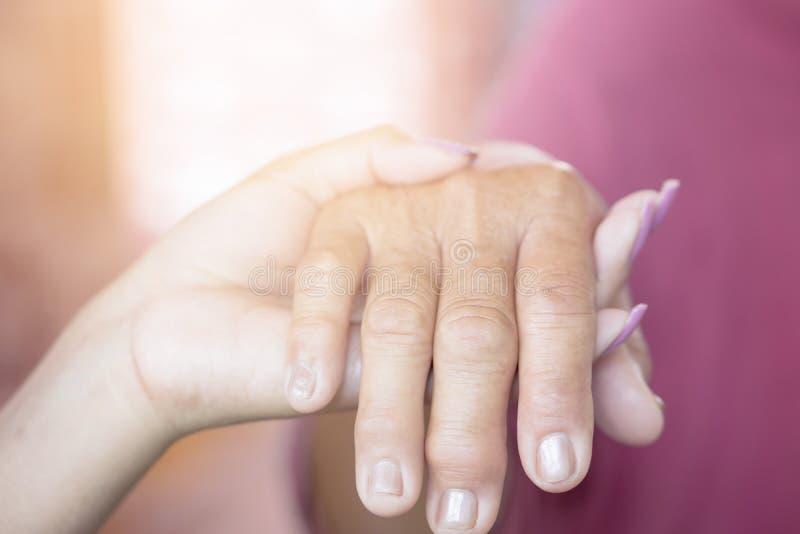 Mano della figlia che tiene la sua mano del ` s della madre il giorno del ` s della madre fotografie stock libere da diritti