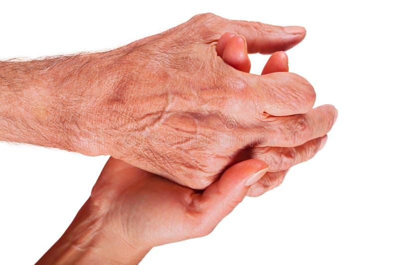 Mano della giovane donna che tiene la mano anziana dell'uomo su fondo bianco immagini stock