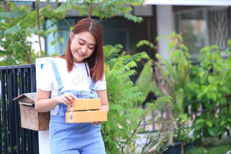 Mano della giovane donna che tiene la scatola marrone del pacchetto a casa, spedente immagini stock