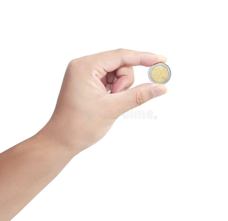 Mano della persona di affari che giudica una euro moneta isolata su bianco fotografia stock libera da diritti