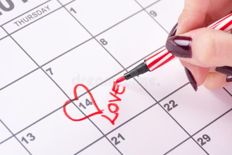 Mano della ragazza con forma ritenuta rossa e la scrittura del cuore del disegno a penna dell'amore di parola nel calendario fotografia stock