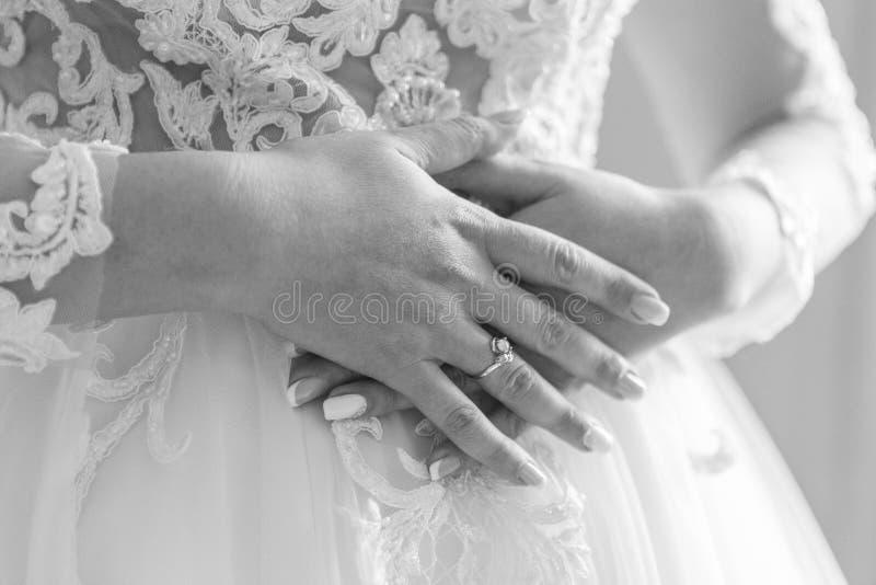 Mano della sposa con l'anello di fidanzamento disposto sul vestito nuziale bianco immagine stock
