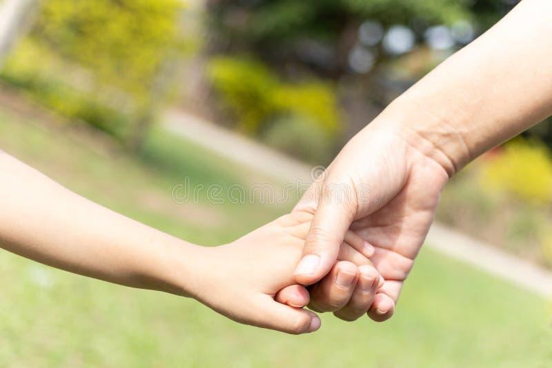 Mano della tenuta del figlio e della madre fotografia stock libera da diritti