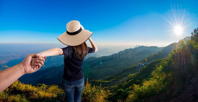 Mano della tenuta della donna del suo marito mentre correndo insieme sulla montagna fotografia stock libera da diritti