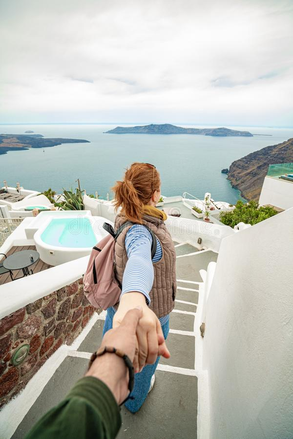 Mano della tenuta della giovane donna e condurre ai posti più bei uno la terra All'isola di Santorini in Grecia, colpo in Thira immagini stock