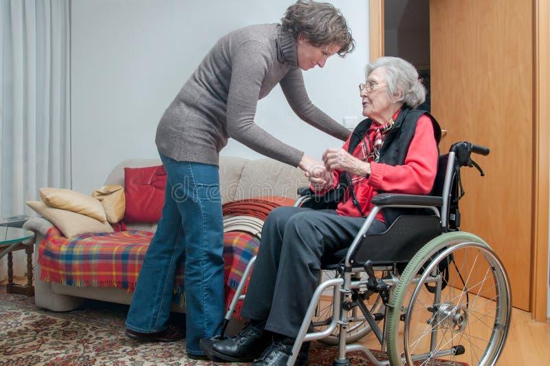 Mano della tenuta della giovane donna della donna senior con la sedia a rotelle fotografia stock libera da diritti