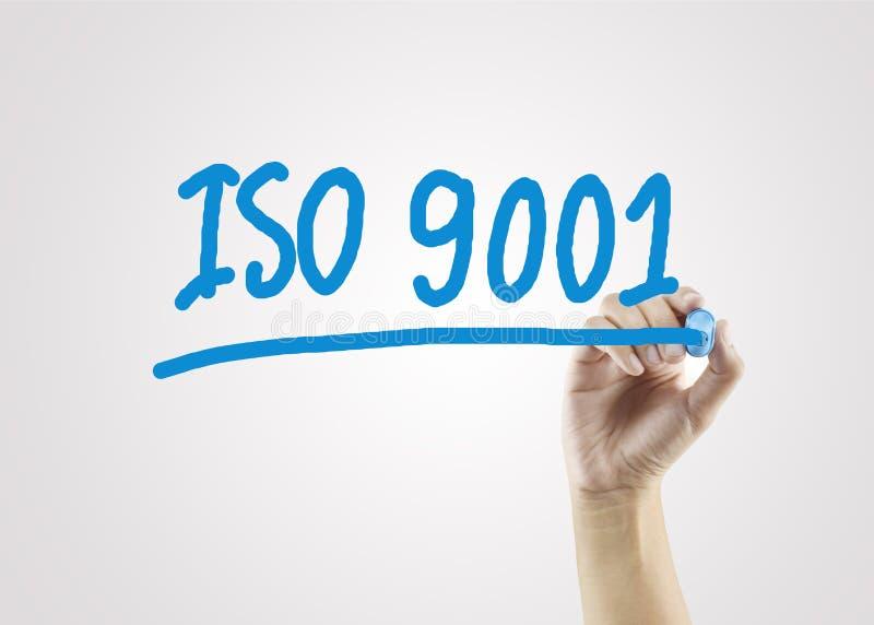 Mano delle donne che scrive ISO9001 sul fondo grigio per l'inizio di affari fotografia stock libera da diritti