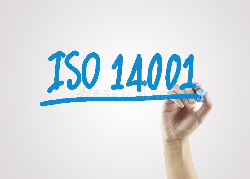 Mano delle donne che scrive ISO14001 sul fondo grigio per lo stra di affari fotografie stock