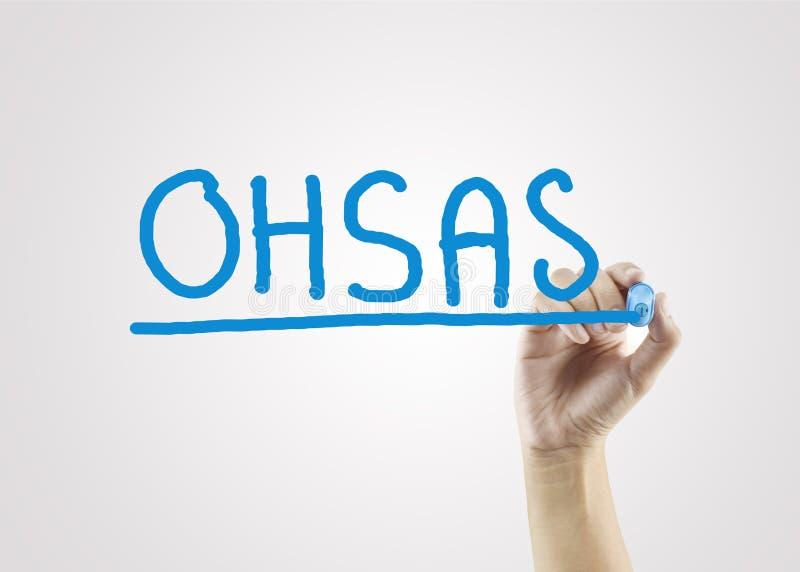 Mano delle donne che scrive OHSAS sul fondo grigio per lo strateg di affari fotografie stock libere da diritti