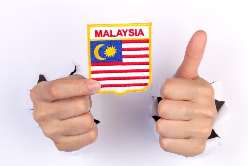 Mano delle donne che tiene la bandiera della Malesia fotografie stock libere da diritti