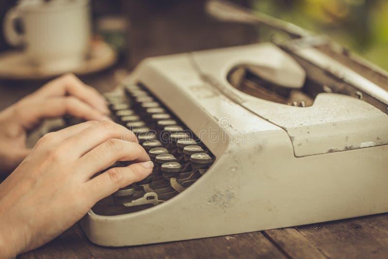 Mano delle donne del primo piano facendo uso di vecchia annata della macchina da scrivere fotografia stock