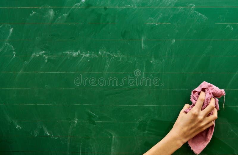Mano derecha de una chica joven que limpia a un consejo escolar verde con una toalla rosada fotografía de archivo libre de regalías