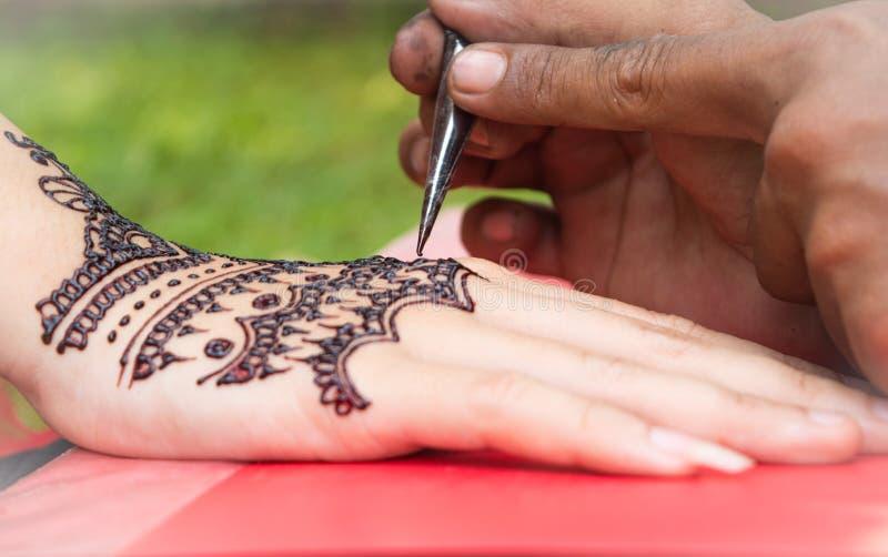 Mano destra della donna sul libro rosso e dipinta con hennè sul giorno delle nozze fotografie stock