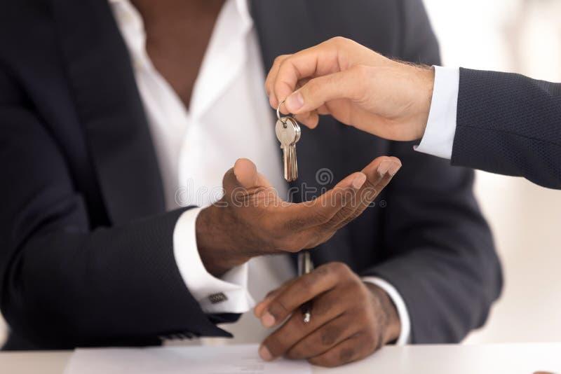 Mano di agente immobiliare che fornisce le chiavi al nuovo padrone di casa africano fotografia stock libera da diritti