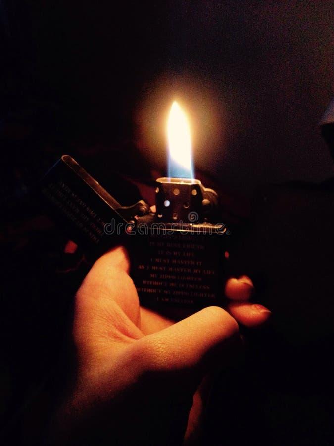 Mano di buio del fuoco dell'accendino della fiamma di Zippo fotografia stock libera da diritti